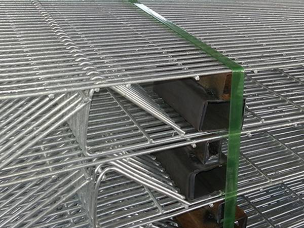 Some brc fence panels which strapped together by a bundle belt are placed one by one in order of face up and face down.