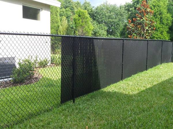 Black chain link fencing with black slats are surrounding the residential backyard.