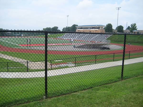 Black chain link fencing fabrics are surrounding the sport field.