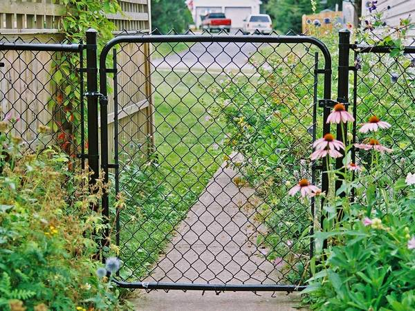 A single gate with chain link fence are installed entrance of garden.