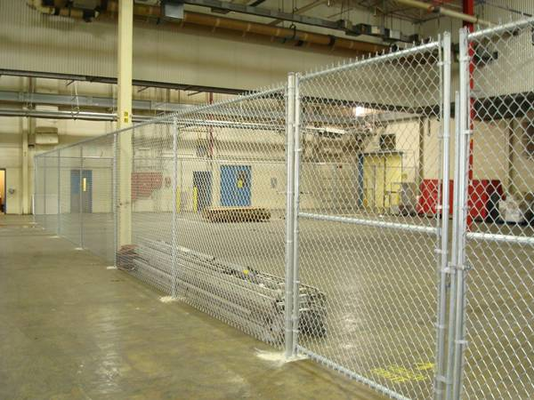 Galvanized chain link fencing are installed in the warehouse and several materials in it.