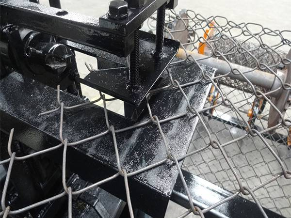A close up picture of chain link fence mesh weaving machine.