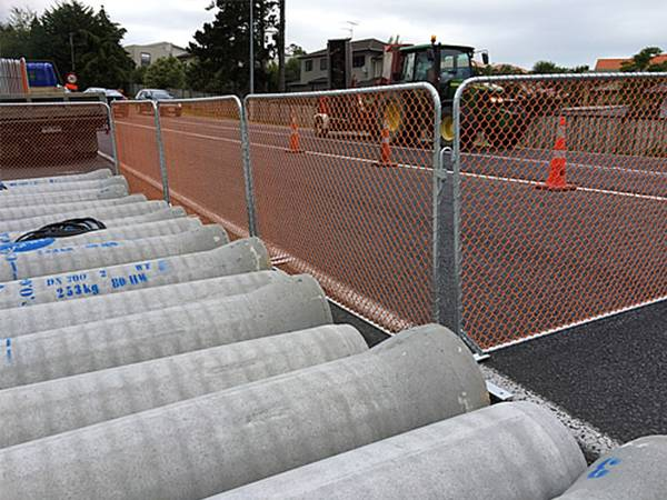 Several construction barriers are standing on the road and several vehicles on the road.