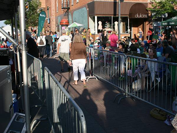 Crowd control barriers are separating a passage way on crowd street.