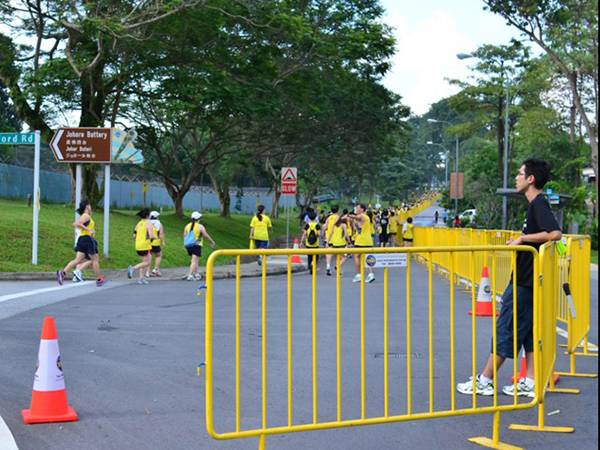 Several runners are running on the road which is enclosed by yellow crowd control barrier.