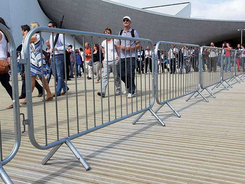 Visitors walk through a pedestrian passageway made up of crowd control barriers.