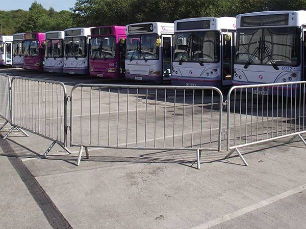 Crowd control barriers are enclosed an area where several bus are parking.