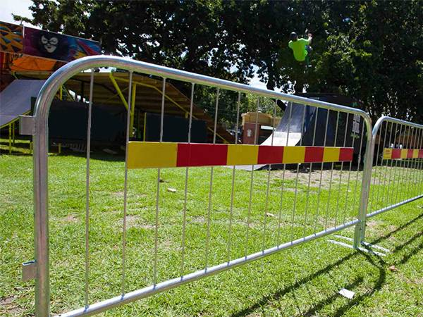 Crowd control barriers are surrounding the stage on the grassland.