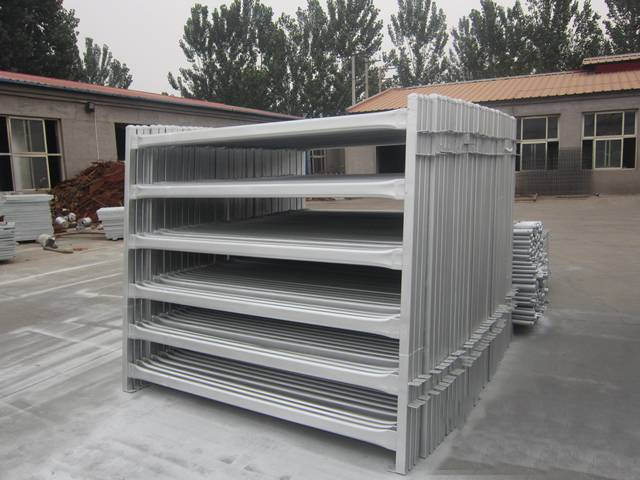 Many galvanized cattle corral panels are on the ground.