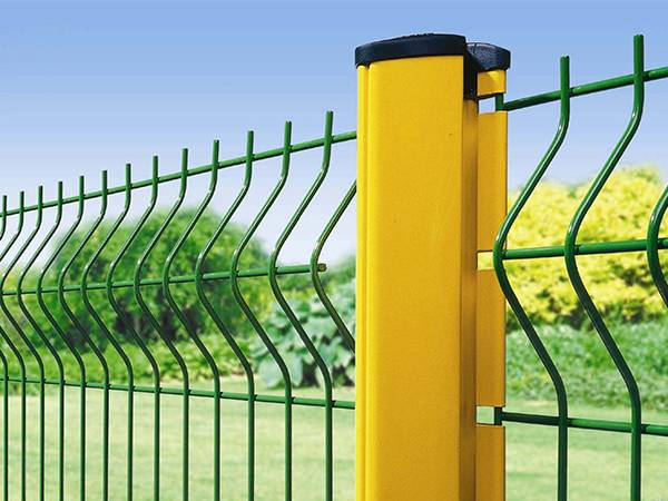 Green security mesh fencing is connected with a yellow peach post.