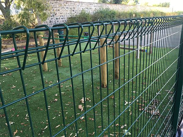 Green roll top fence is installed in playground to protect children's safety.