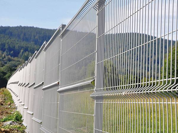 Long white 3D security fences are installed on a slope.