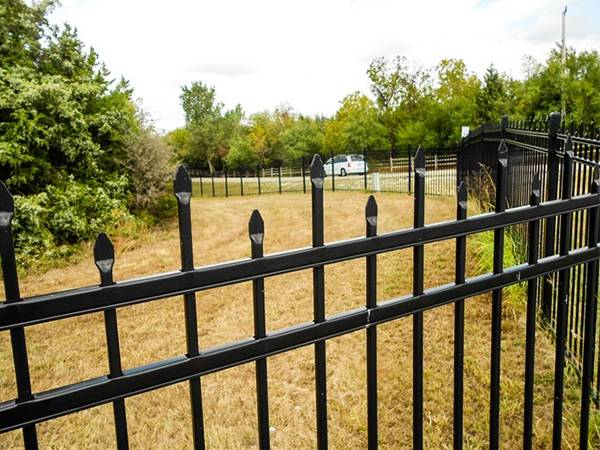 Black ornamental steel tubular fence with staggered spear top.