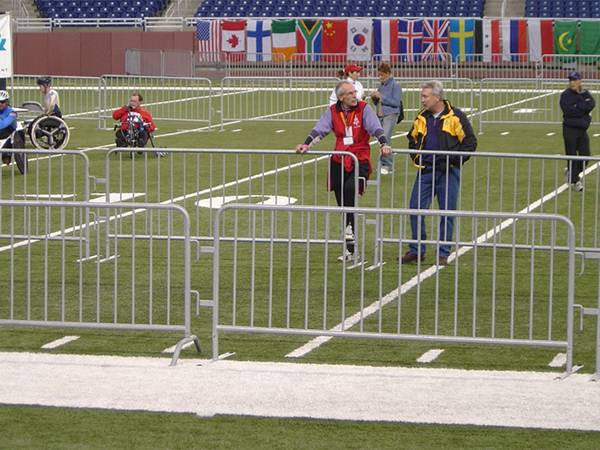 Several workers in the sport field, which is surrounded by crowd control barriers.