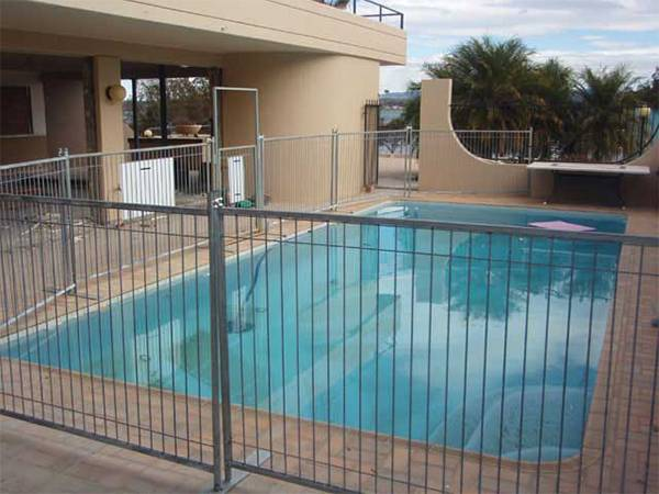 Several temporary pool fencing panels are surrounding the private villa swimming pool.