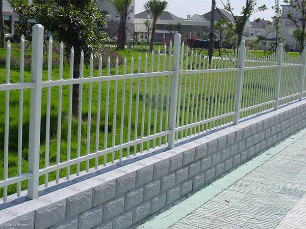 Gray ornamental steel tubular fence with wavy spear top.